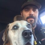 Mark and His Beagle Dog Benson in the truck. Benson is looking right into the camera.