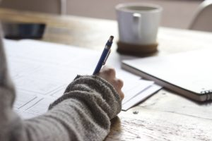 A person writing in a diary at a desk with coffee in the background. The person's hand is writing with a pen in their right hand.